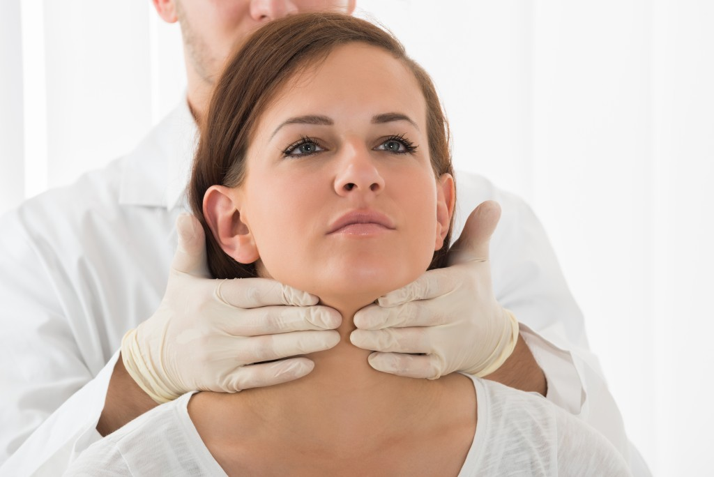 doctor checking throat of woman