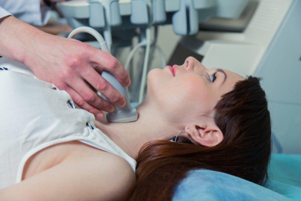 doctor examining throat of patient