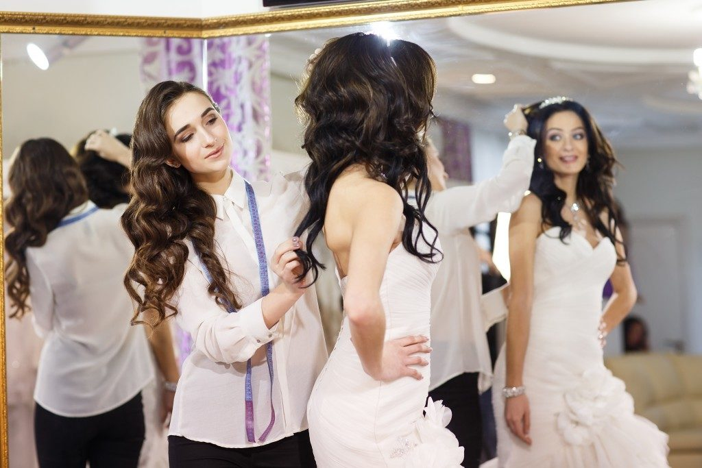 Female trying on wedding dress in a shop with women assistant