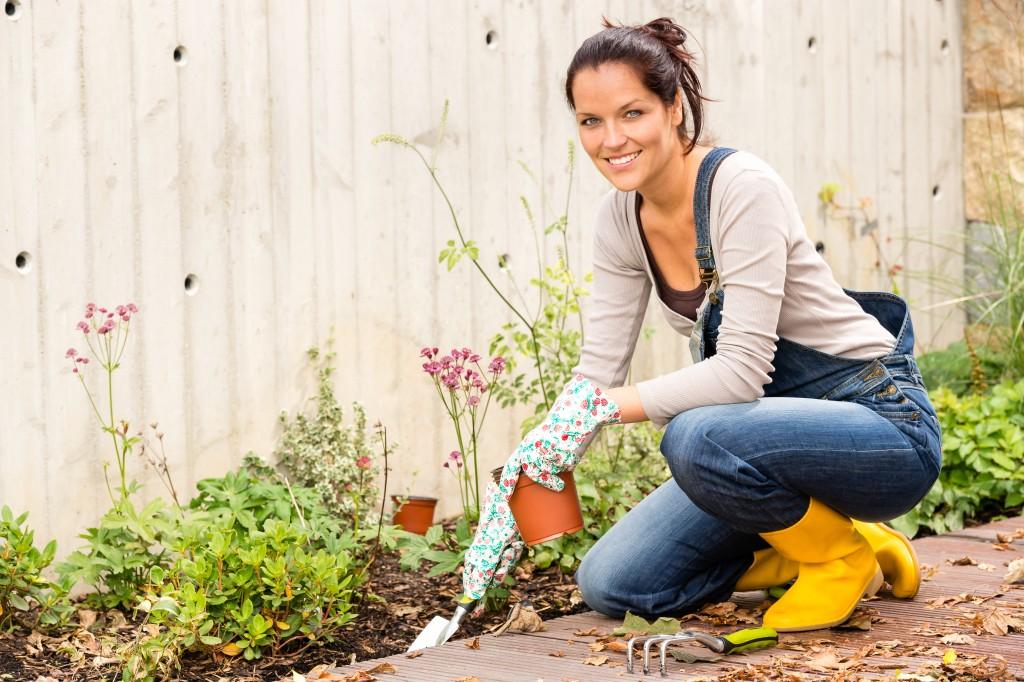 Woman planting floering plants in her garden