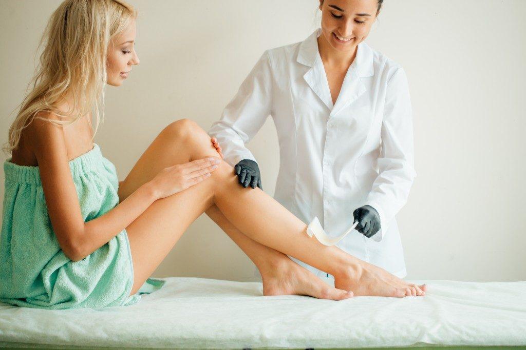 woman having legs waxed