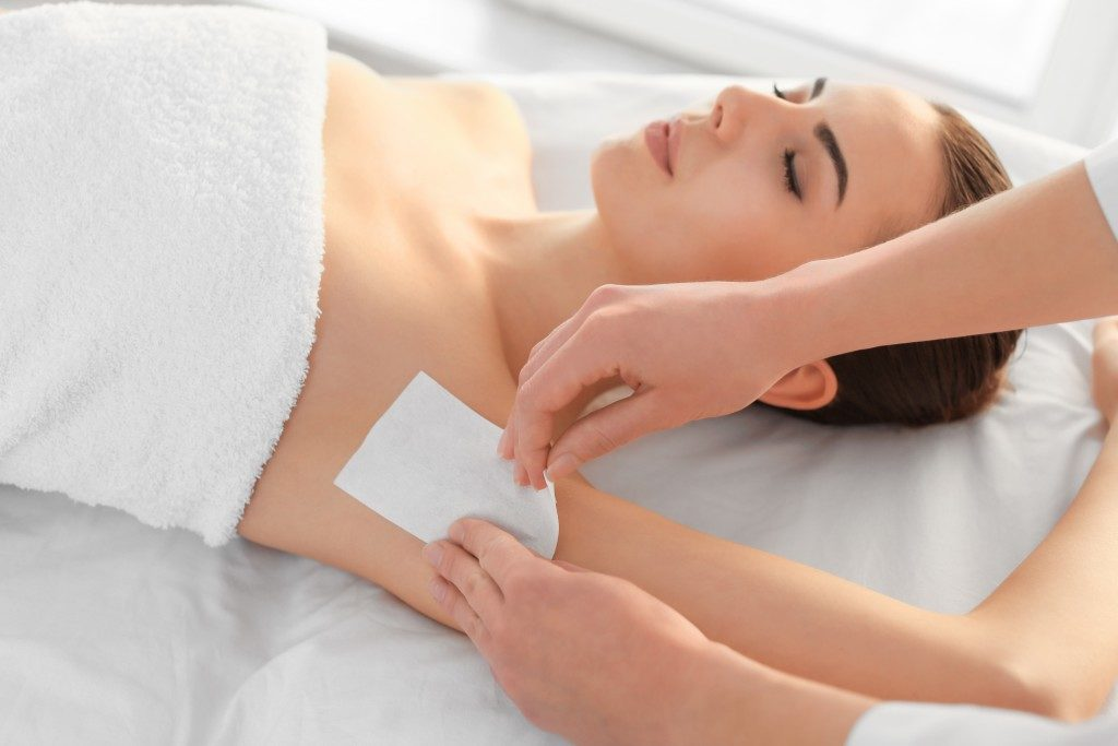 woman having armpits waxed