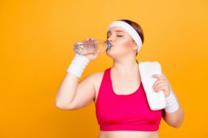 woman in working out clothes drinking water