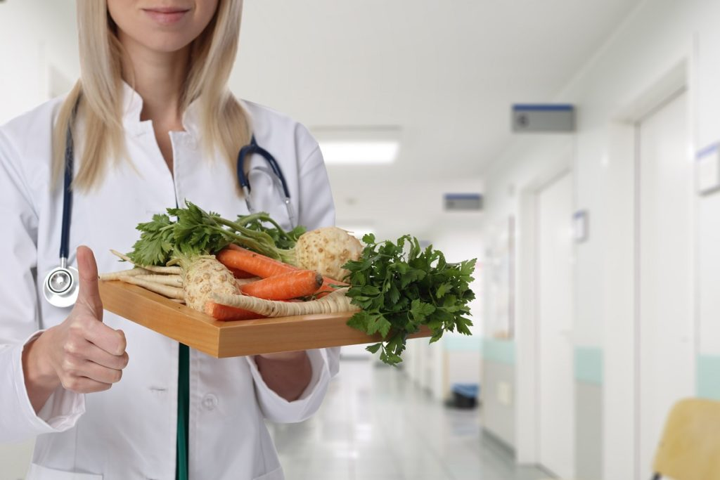 doctor holding plate full of vegetables