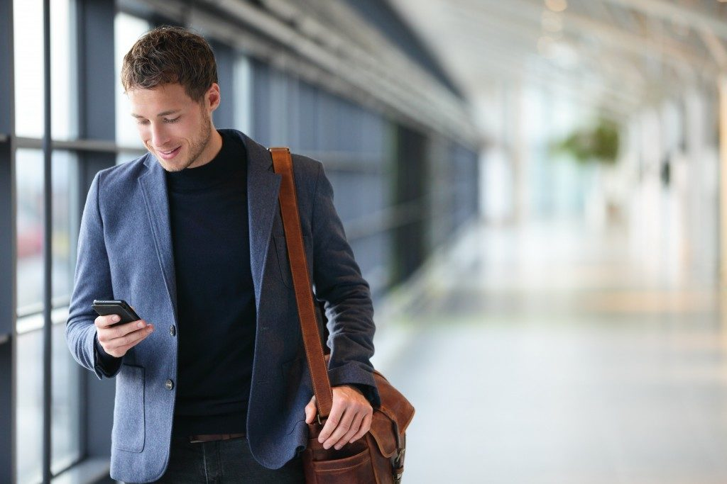man on smartphone wearing a blue suede jacket