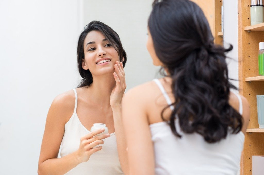 Woman caring of her beautiful skin on the face standing near mirror in the bathroom. Young woman applying moisturizer on her face. Smiling girl holding little jar of skin cream and applying lotion.