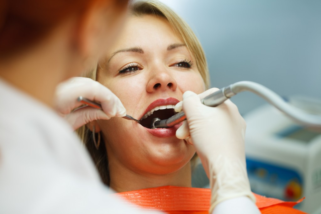 Female having her teeth examined by a dentist