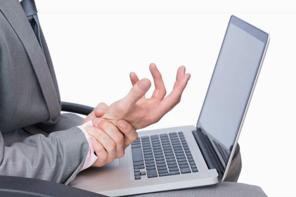 Close-up of business man with wrist pain while using laptop over white background