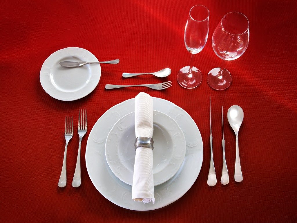 Perfect table setting on red cloth background