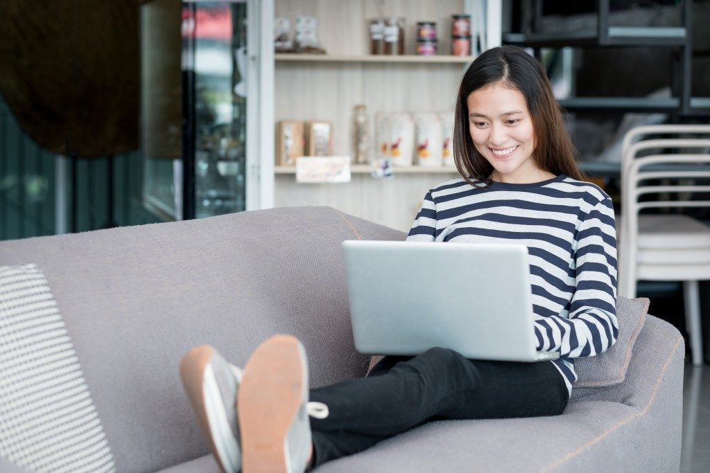 woman using her laptop while sitting on the couch