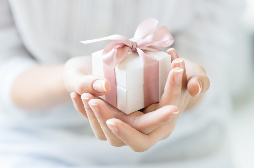 hands of woman holding a gift wrapped in pink ribbon