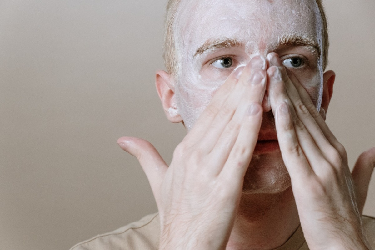 man cleansing his face